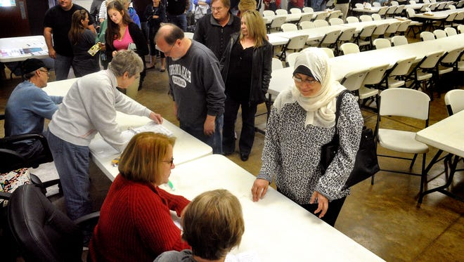 Voters stand in line to register before casting their ballots at the polling place in the Espy Fire Hall near Bloomsburg, Pa., on Tuesday, Nov. 8, 2016. Long lines were reported at several polling places throughout the area. (Bill Hughes/Bloomsburg Press Enterprise via AP)