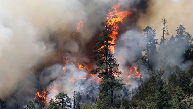 In this Saturday, June 9, 2018 photo, a wildfire burns on the east side of Hermosa Cliffs near Hermosa, Colo.
