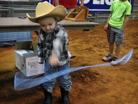 Grady Boone, 2, plays with a lasso he helped make at