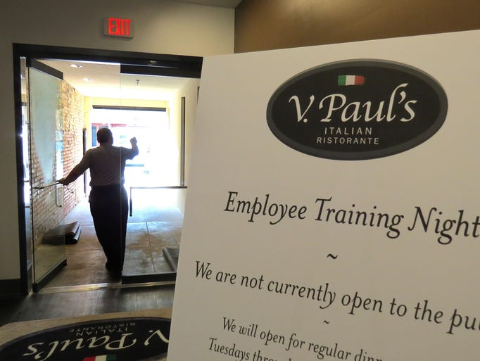Wednesday morning Father Joseph Callipare, from the Basilica of St. Michael the Archangel, blesses the front of V. Paul's Italian Ristorante soon to open in downtown Pensacola at 29 Palafox Place.
