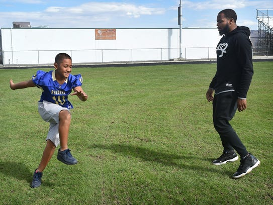 Duke Williams works with 9-year-old Sione Kaho at Hug