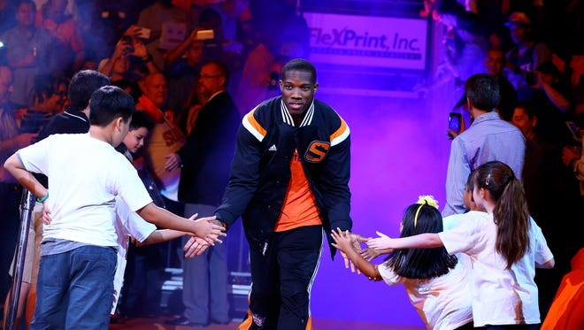 Suns guard Eric Bledsoe runs out to greet fans before the season opener vs. the Lakers on Oct 29, 2014 in Phoenix.