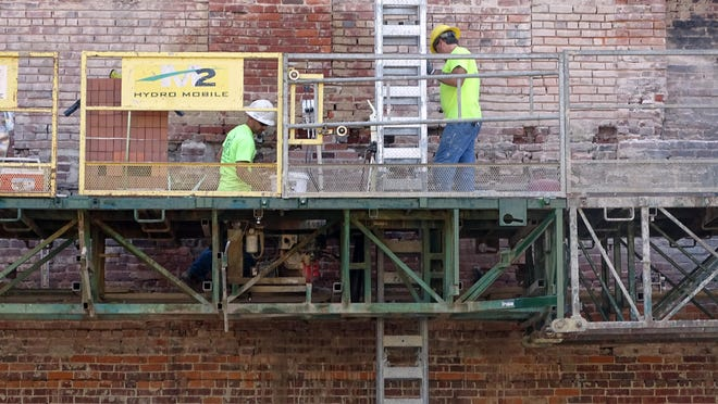 Mike Barbee, left, and Rodney Copley, both of Lang Masonry from Waterford, restore a brick wall that once belonged to the Park Hotel and will soon serve as a focal point for the artPARK, now under construction on Main Street.