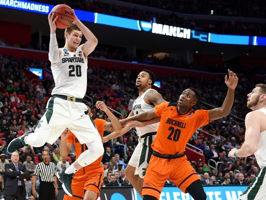 Michigan State's Matt McQuaid, left, grabs a rebound
