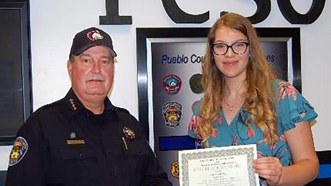 Pueblo County Sheriff Kirk Taylor presents a $1,000 scholarship to Sierra Dobney of Pueblo West High School.