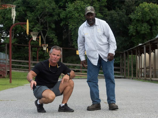 Baker High School Football coach and athletic director, Matt Brunson, and district employer, Danny Thomas, Sr. who grow up with Houston McTear, stand on the start line of the school's old track where McTear became a world-class runner.