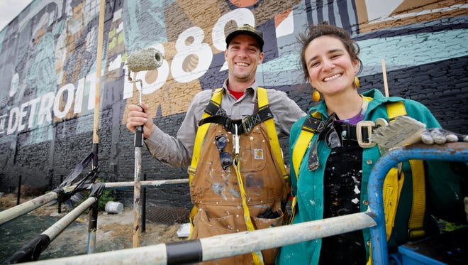 Kelly Golden, 28, and Jordan Zielke, 28, both of New Baltimore, Mich, photographed during their break as they work on a new mural on on Monday, Aug. 24, 2015, on the wall of the new Carhartt store in Detroit.