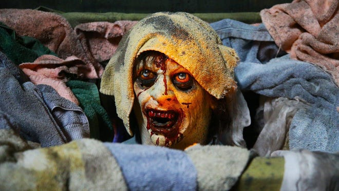 A creepy head pokes out of a hamper in the locker room of the Haunted Schoolhouse last week.