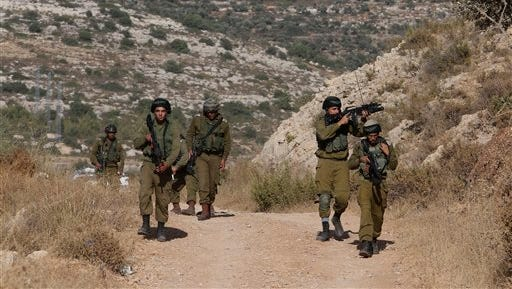 """Israeli soldiers search the area where a Palestinian man shot two Israeli men near the Dolev settlement, northwest of West bank city of Ramallah, Friday, June 19, 2015. A lone gunman opened fire at a car killing an Israeli man and wounding another in what police said was a """"terror attack."""" (AP Photo/Nasser Shiyoukhi)"""