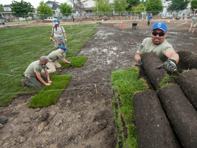 Fresh sod is laid down for a new soccer field during
