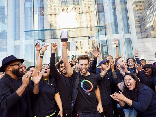 Apple team members cheering a customer holding up a new iPhone outside of an Apple store.