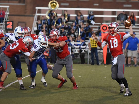SJCC's Spencer Harrison throws a pass Saturday against Danville as Nate Burns, middle, and Ross Snyder block.