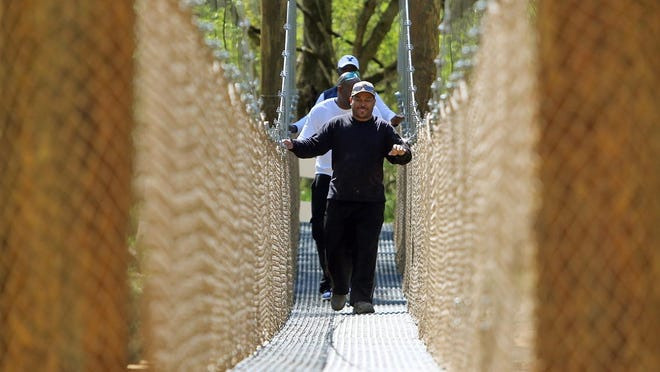 Ray Ford, Anthony Potlow and Tyrone Beam are seen crossing the suspension bridge at the First Broad River Trail in Shelby before the structure was destroyed.