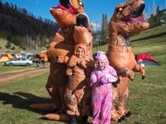 Bundled up for high mountain wind, two campers were greeted by friendly dinosaurs as they enjoyed the play area for children during the Wind Rider Music Festival..