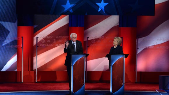 Hillary Clinton listens as Bernie Sanders speaks during