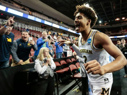 March 17, 2018 – U-M vs. Houston: Jordan Poole celebrates with fans as he runs off the court after scoring the buzzer-beater to defeat Houston 64-63 at INTRUST Bank Arena in Wichita, Kan.