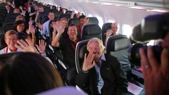 Sir Richard Branson, front, waves with other employees