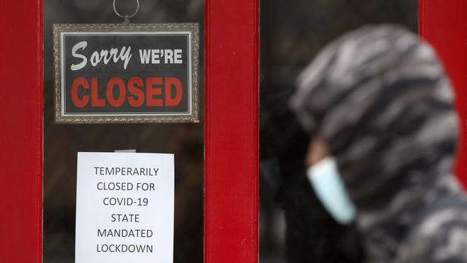 FILE - In this May 7, 2020 file photo, a pedestrian walks by The Framing Gallery, closed due to the COVID-19 pandemic, in Grosse Pointe, Mich. The U.S. unemployment rate hit 14.7% in April, the highest rate since the Great Depression, as 20.5 million jobs vanished in the worst monthly loss on record. The figures are stark evidence of the damage the coronavirus has done to a now-shattered economy..