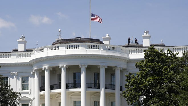 FILE - In this July 18, 2020, file photo, a U.S. flag flies at half-staff over the White House in Washington in remembrance of Rep. John Lewis, D-Ga. President Donald Trump did not pay his respects when Lewis lay in state in the Capitol Rotunda. Iwas another break in convention for a president who has broken so many norms, and one that underscored his separation from much of Washington society, along with his dismal relationship with Democrats on Capitol Hill -- especially members of color.
