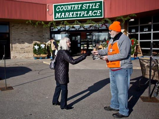 Volunteer Tom Gillette, of Port Huron, takes a donation