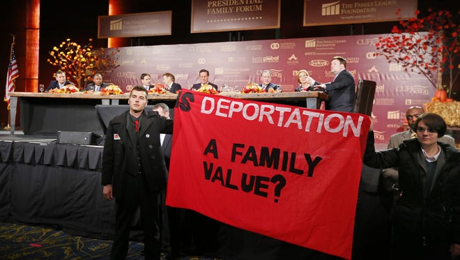 Anti-deportation protesters interrupt the Presidential Family Forum in Des Moines Friday, Nov. 20, 2015.
