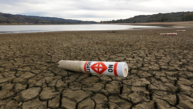 In this Feb. 4 2014 file photo, a warning buoy sits on the dry, cracked bed of Lake Mendocino near Ukiah, Calif.  State officials reported Tuesday, Feb. 3, 2015, that residents in drought-stricken California met Gov. Jerry Brown's call to slash water use by 20 percent for the first time in December, when water use fell by 22 percent compared to the same month in 2013.