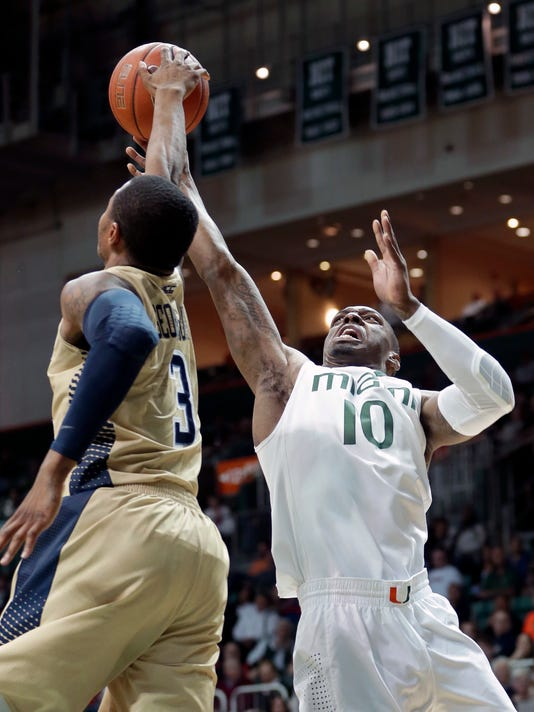 Georgia Tech forward Marcus Georges-Hunt (3) blocks a shot by Miami guard Sheldon McClellan (10) during the first half of an NCAA college basketball game in Coral Gables, Fla., Wednesday, Jan. 28, 2015. (AP Photo/Alan Diaz)