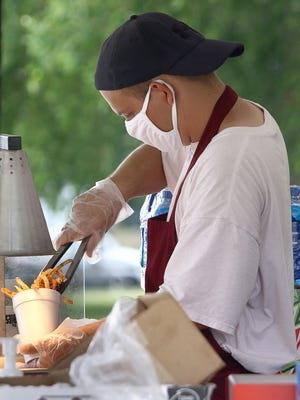 """Darrell """"Bubdog"""" Claypool loads french fries into a large cup inside Richardson's French Fries out of New Middletown for a customer waiting in their car on Saturday, July 11, 2020 during the weekend long Fair Food Extravaganza 2 held at the Canfield Fairgrounds."""