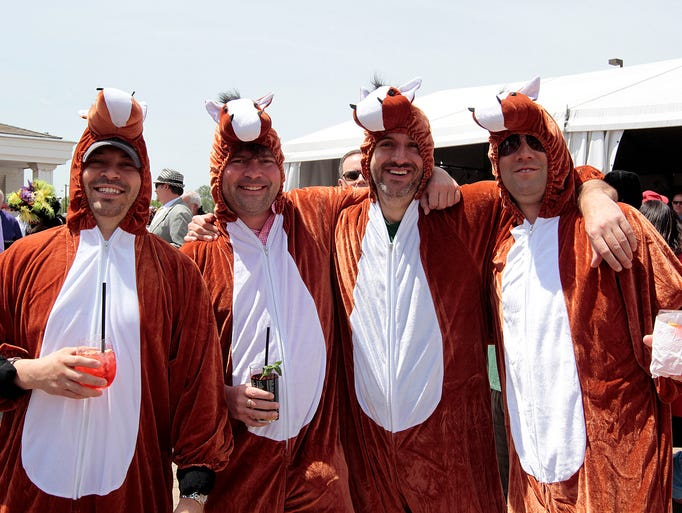 Dressed as horses, from left, Pablo Reyna, Paul Henderson, Jason LeuVoy and Harley Goldstein pose for a picture Saturday at Kentucky Derby 140 at Churchill Downs in Louisville, Ky. May 3, 2014.