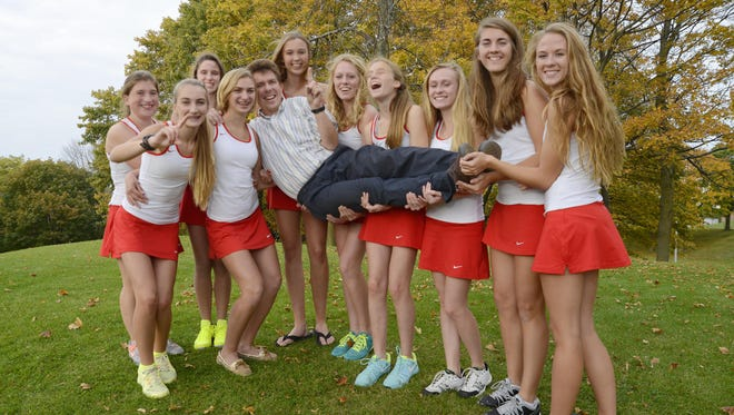 Manitowoc Lincoln girls tennis team holds up their coach Jacques Verbauwhede for a portrait at the school on Tuesday. From left: Moriah Hansen, Allyson Verbauwhede, Bailey Budnik, Sydney Verbauwhede, Julie Rohrer, Maddie Sheedlo, Halimae Laurino, Isabella Ramminger, Jen Belisle and Dayna Decker.