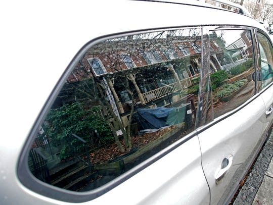 The home of the shooting victim is reflected in a car