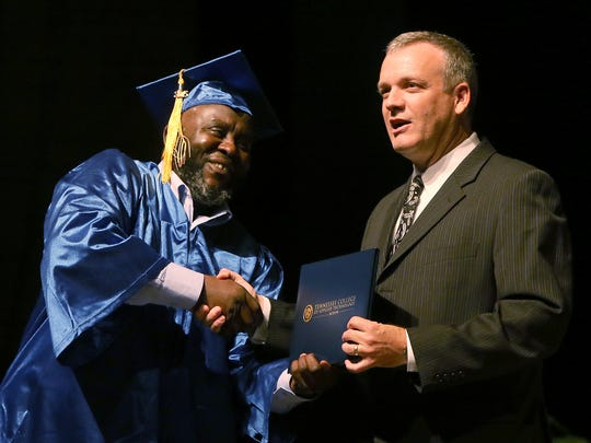 Abdalla Khalafalla shakes hands with Tennessee College of Applied Technology of Jackson Director Jeff Sisk as he receives his diploma in Administrative Office Technology during the 2015 TCAT graduation ceremony at the Carl Perkins Civic Center in Jackson, Tenn., on Tuesday, Aug. 25, 2015.