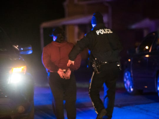 A woman is escorted away in handcuffs from the scene
