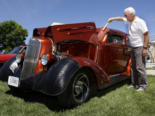 Russ Treiner of Great Falls dusts his 36 Chevy before the Dutton Fun Day car show begins Saturday.