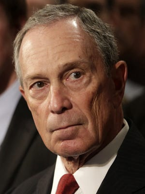 New York City Mayor Michael Bloomberg, second from left, watches a video testimonial surrounded by shooting survivors and victims' relatives during a news conference in City Hall in New York, Monday, Dec. 17, 2012. New York Mayor Michael Bloomberg and dozens of shooting survivors and victims' relatives are calling on Congress and President Barack Obama to tighten gun laws and enforcement. (AP Photo/Seth Wenig)
