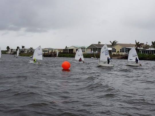 Twenty-two Optimist dinghies in two fleets, sailing