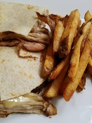 Banyan 320 Kitchen and Bar's Cuban on a gluten-free wrap made of soy, rice, potato, and chia with slow roasted pork, ham, pickles, Swiss cheese and grainy brown mustard. It was accompanied by hand-cut fries served with a ramekin of ketchup.