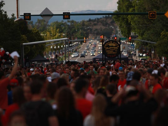 A crowd of people walk around Main Street in Cedar City during Southern Utah University's 'Paint the Town Red' event, Thursday, Aug. 27, 2015.
