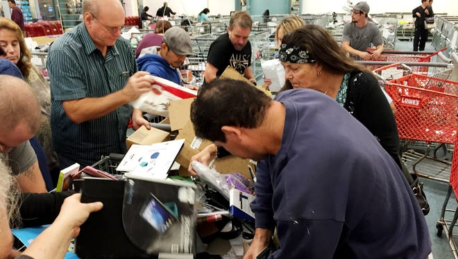 """Shoppers dig for treasures at the """"GimmeA5"""" liquidation store at RiverGate Mall."""