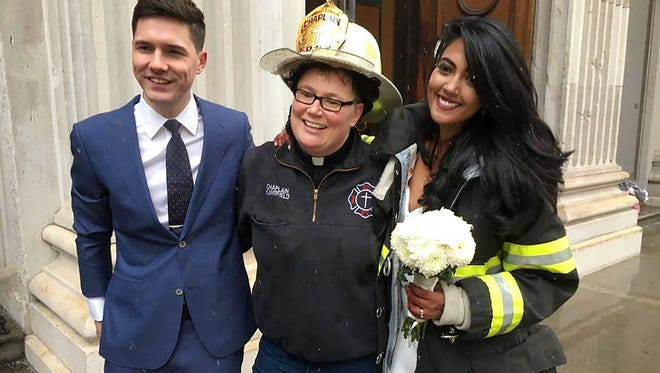 Aaron Vanderhoff, Fire Department of New York Chaplain Ann Kansfield and Nesh Pillay stand outside Tweed Courthouse in New York City. Kansfield performed the wedding ceremony between the two following a crane crash that killed one in NYC.