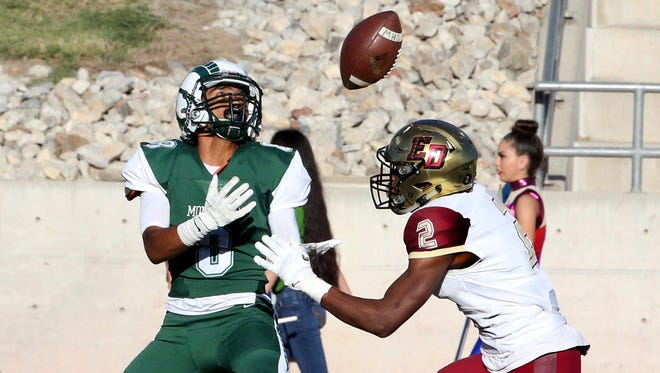 Montwood wide receiver Daniel Aguilar, left, catches a long throw for a touchdown against El Dorado defensive back Davion Kinsey on Thursday at the Socorro Activities Complex.