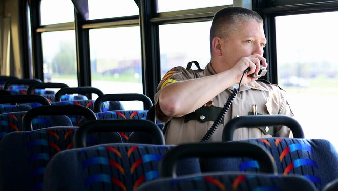 Tennessee Highway Patrol Sgt. Jeromy Edwards radios in a distracted driver from one of the THP buses, Monday, April 10. THP and the Tennessee Highway Safety Office partnered with local law enforcement for Tennessee's first statewide distracted driving enforcement bus tour.