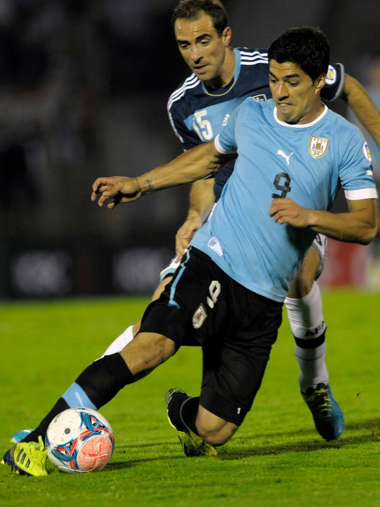 FILE - In this Oct. 15, 2013, file photo, Uruguay's Luis Suarez, front, fights for the ball during a 2014 World Cup qualifying soccer game in Montevideo. (AP Photo/Matilde Campodonico) - SEE FURTHER WORLD CUP CONTENT AT APIMAGES.COM