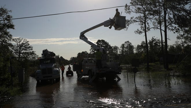 A crew contracted by LCEC restores power to a neighborhood in North Fort Myers on Tuesday. Hurricane Irma caused widespread power outages throughout the state.