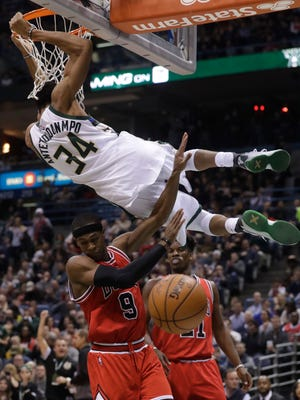 Giannis Antetokounmpo dunks over the Chicago Bulls' Rajon Rondo (9) and Jimmy Butler during the second half of an NBA basketball game Thursday, Dec. 15, 2016, at the BMO Harris Bradley Center.