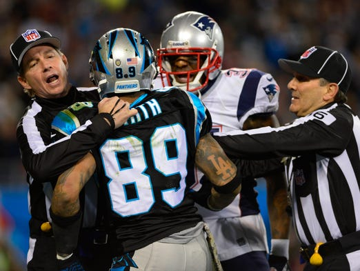 Officials separate Panthers receiver Steve Smith (89) and Patriots cornerback Aqib Talib during the first quarter of their Monday night contest.