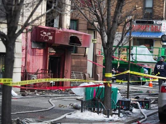 Debris litters the sidewalk in front of Harlem building