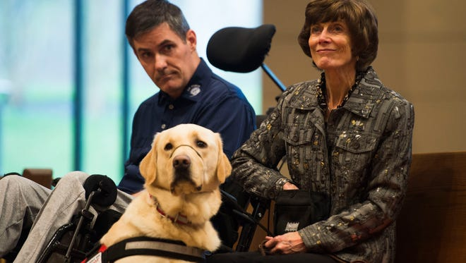Retired Air Force Col. Shawn Pederson, dog Vanner, and Karen Pederson listen during a ceremony formally giving Vanner to Shawn at Tellico Village Community Church in Tellico, Thursday, March 1, 2018.
