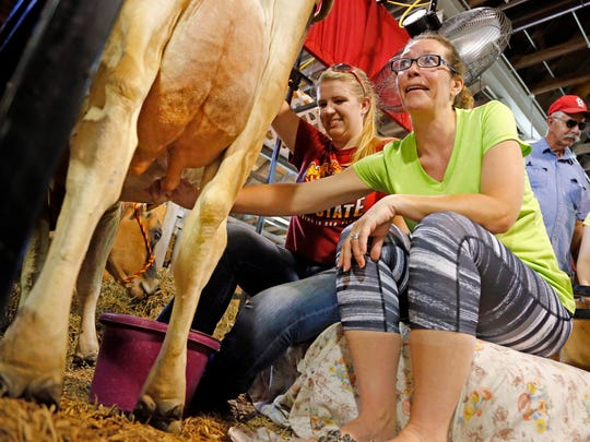 Heidi Niles of muscatine learns to milk a cow from Celina Young, a Junior at Iowa State University at the Iowa State Fair Friday, Aug. 14, 2015.