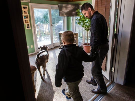 Carl Kapes walks his eight year-old son Brayden out to the back yard, along with their family dog Boomer, at their home in Wilmington on Wednesday afternoon, October 26, 2016.